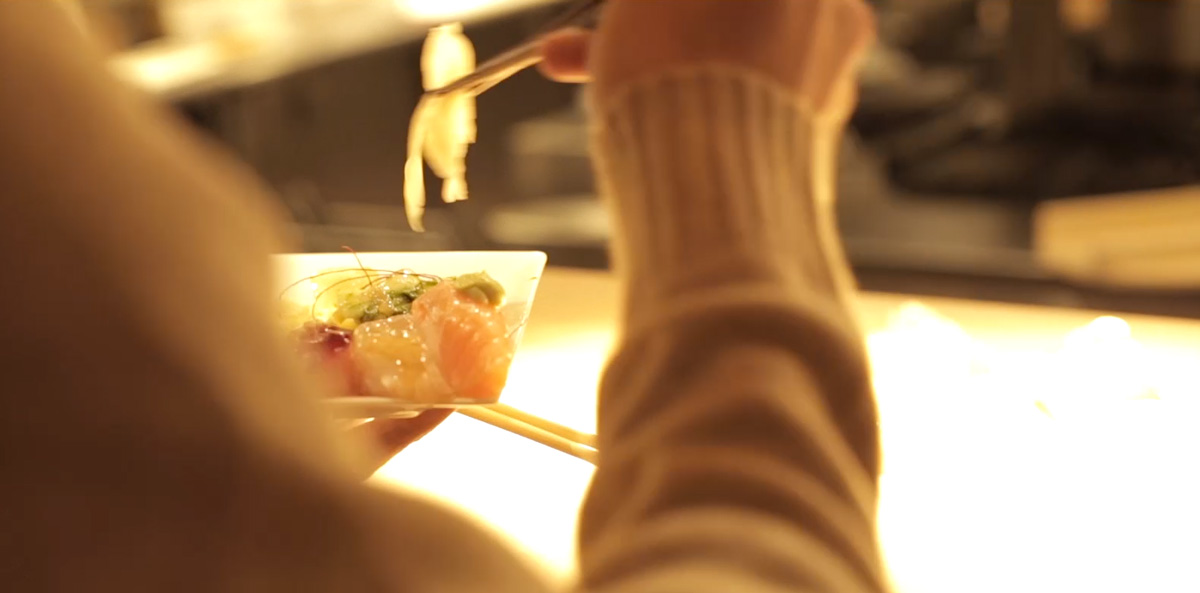 Customer holding sushi in chopsticks