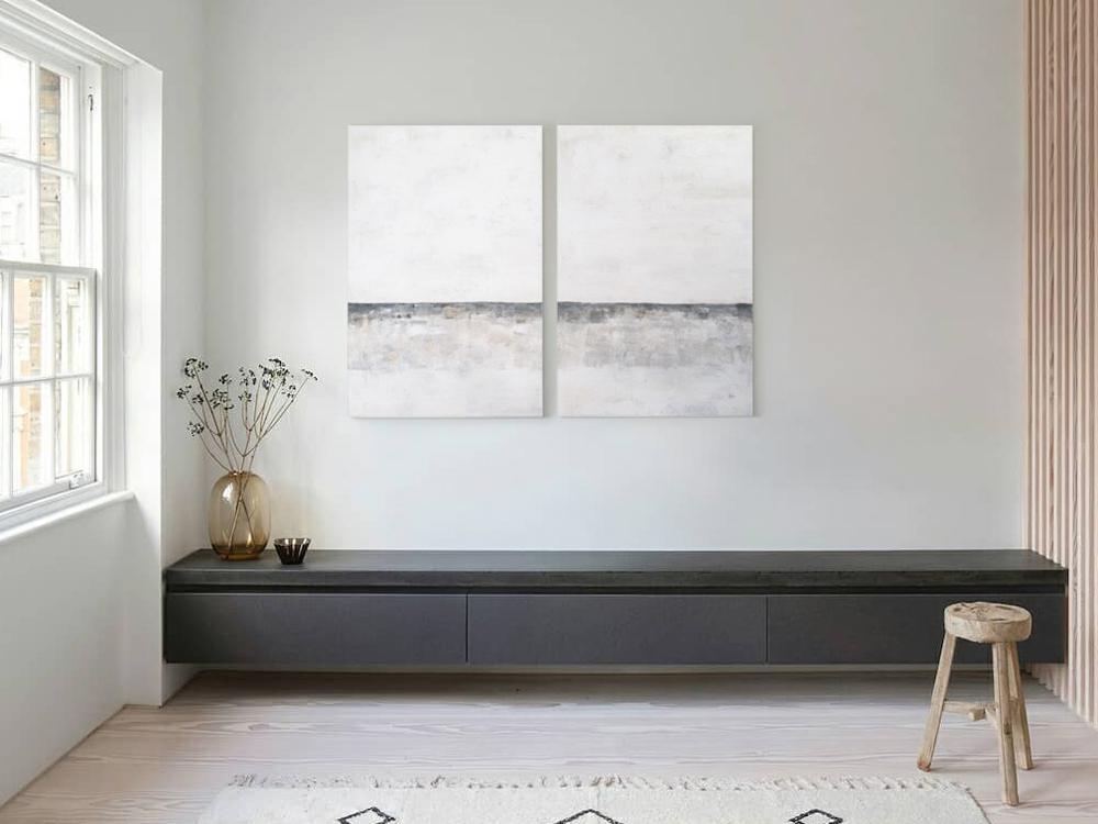 Obra Septiembre colgada en pared de salón sobre mueble negro