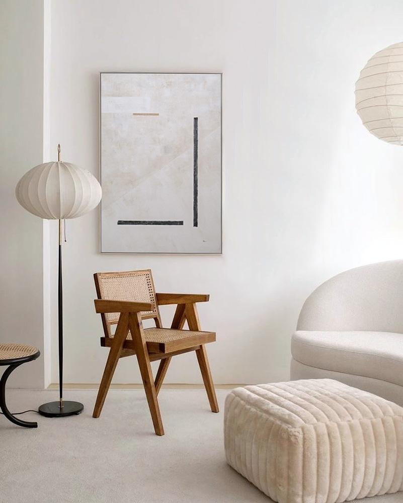 Obra Elementos I colgada detrás de silla de diseño en salón