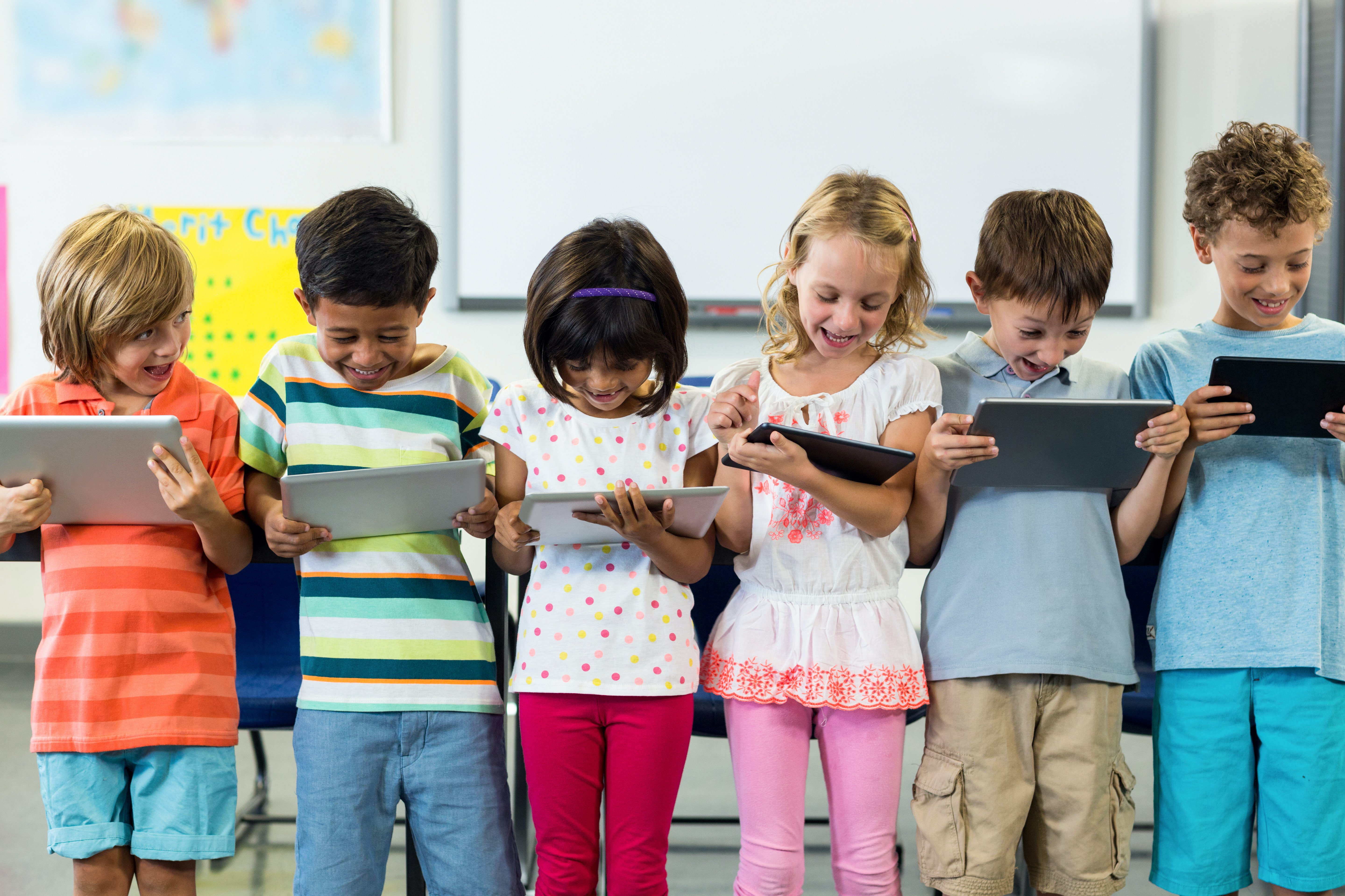 young children reading books in multi colored shirts