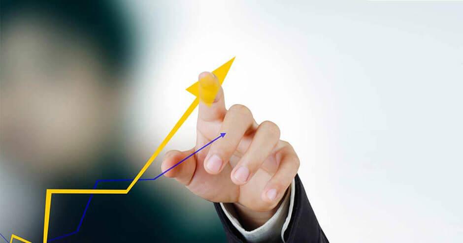 Imagem de uma mão fazendo crescer a curva de um gráfico.