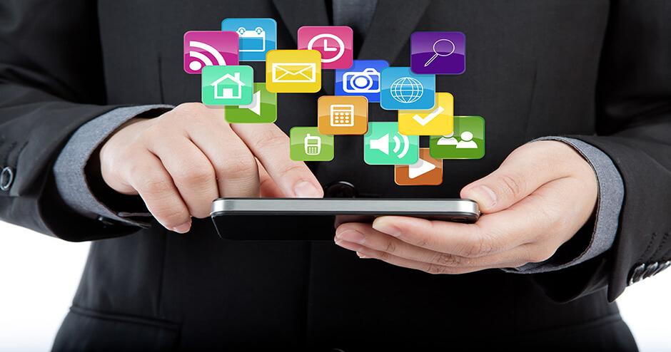 Imagem de um homem segurando um tablet com muitos aplicativos em volta.