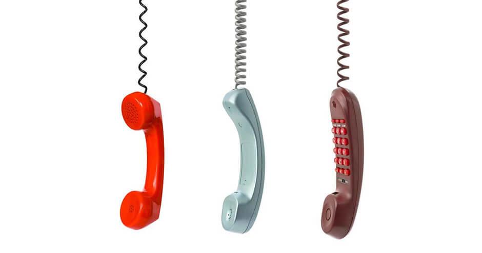 Imagem com 3 telefones coloridos pendurados pelo cabo.