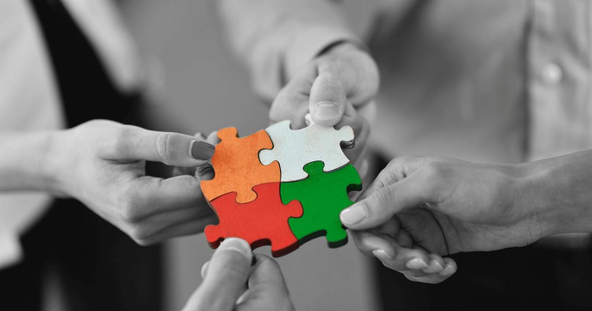 Imagem de 4 mãos juntando pedaços de um quebra-cabeça coloridos.