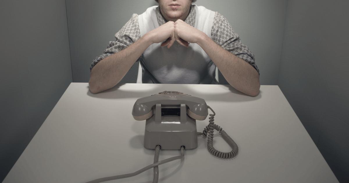 Homem sentado em uma mesa olhando para um telefone.