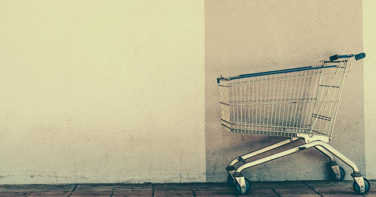 Carrinho de compras vazio encostado na parede.