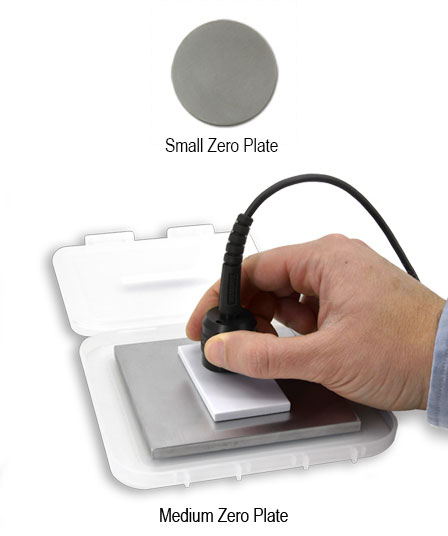 Image of both the Small Zero Plate and the Medium Zero Plate. A hand is measuring the Medium Zero Plate with a probe