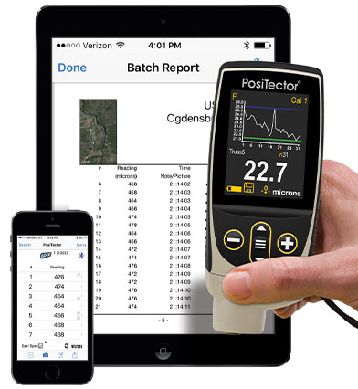 Image of PosiTector gage body held in hand in front of a smart phone and tablet, both with the PosiTector App on them