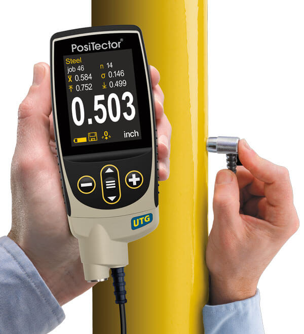 Image of PosiTector UTG M measuring the thickness of a yellow pipe; stats mode is on the screen