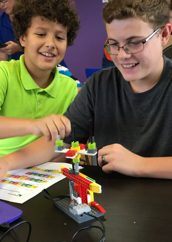 Two boys playing a game with motorized  LEGO bricks