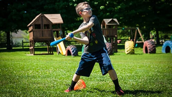 A young boy playing with a ball on a fieldDescription automatically generated