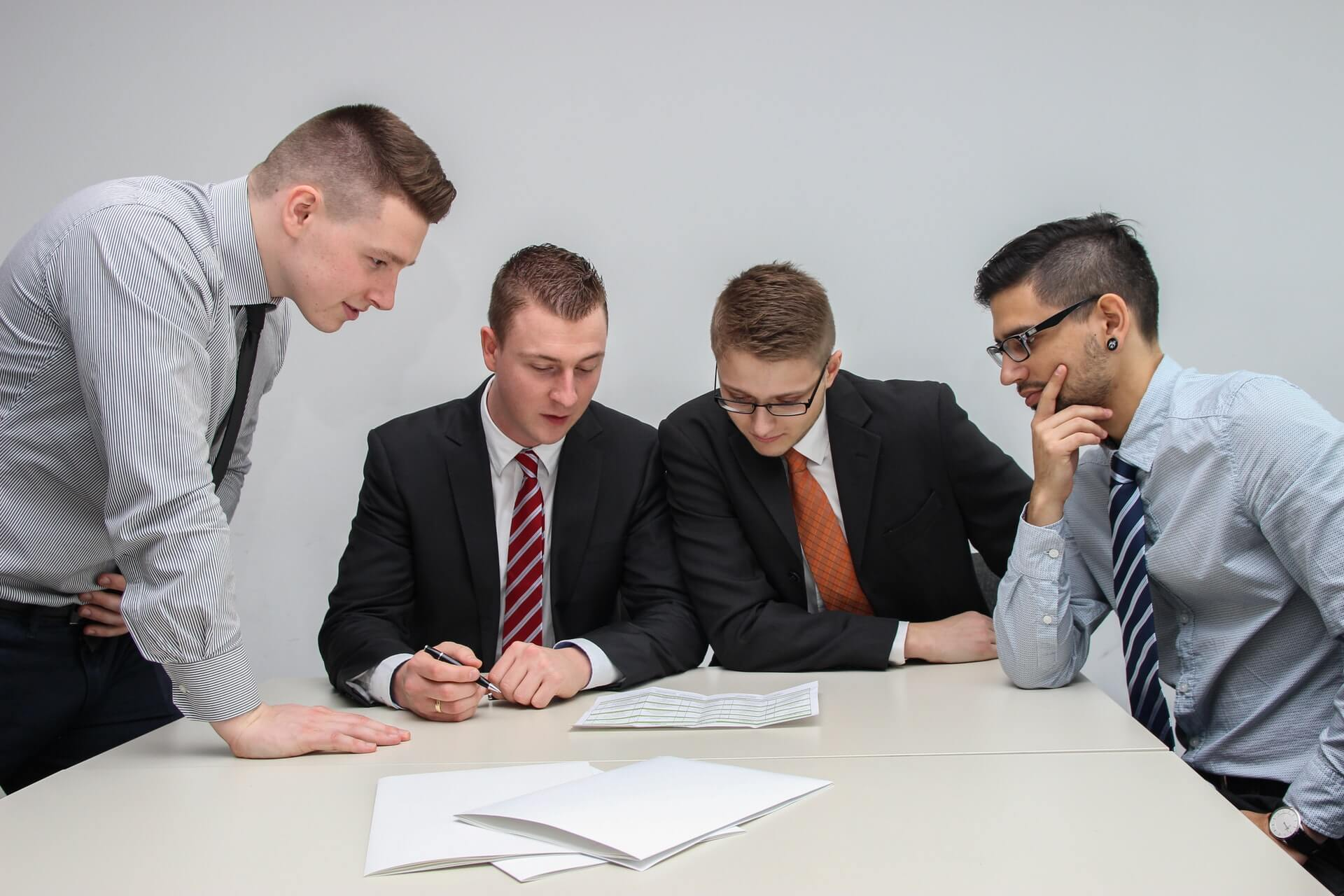 four men looking at a document