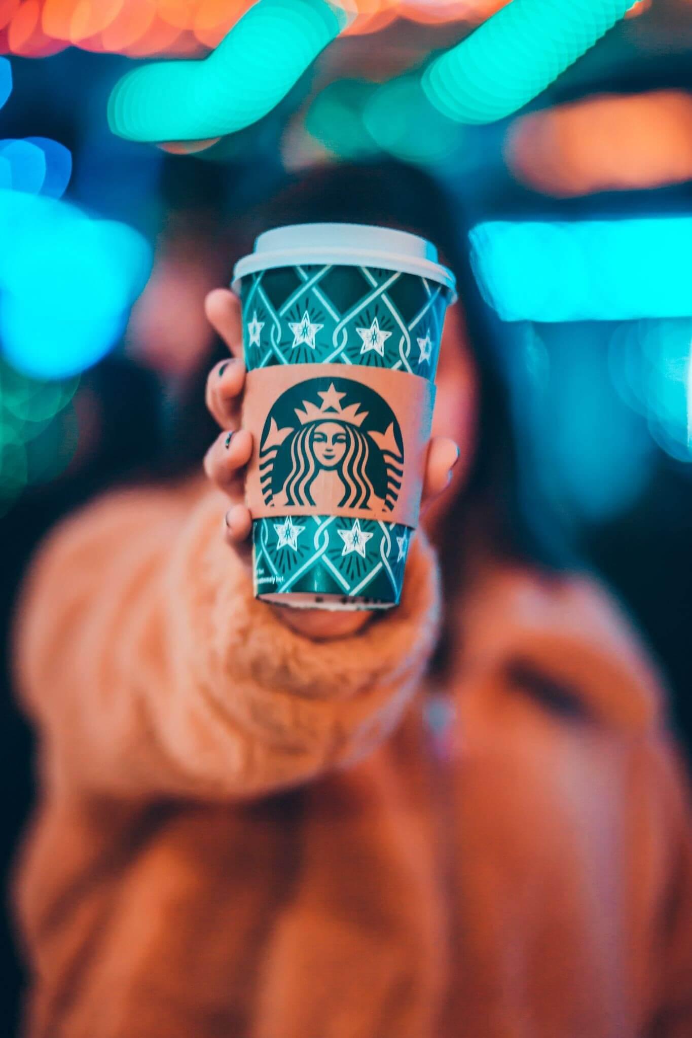 Starbucks brand ambassador holding a coffee