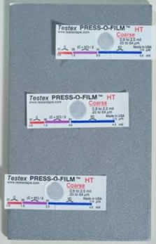 Photo displaying 3 pieces of replica tape on a blasted substrate.