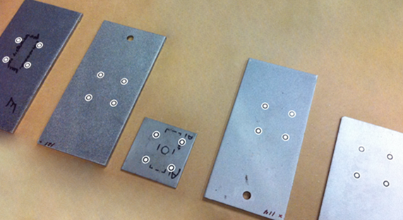 Photo displaying 5 blasted steel test panels used in the round robin (ASTM) study cited in the article.