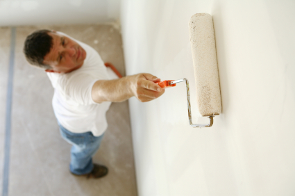 Photo of a man painting drywall using a roller-brush.