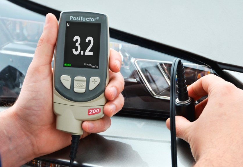 Close-up photo of a PosiTector 200 measuring the paint thickness on a plastic car bumper