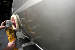 Photo of a person detailing an automobile with an orbital polisher