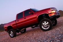 Photo of red pickup truck on gravel