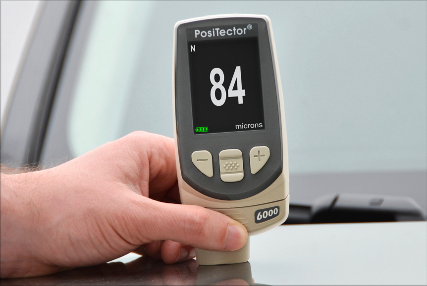 Close-up photo of a PosiTector 6000 in Non-Ferrous Mode taking a paint thickness measurement on an automobile hood