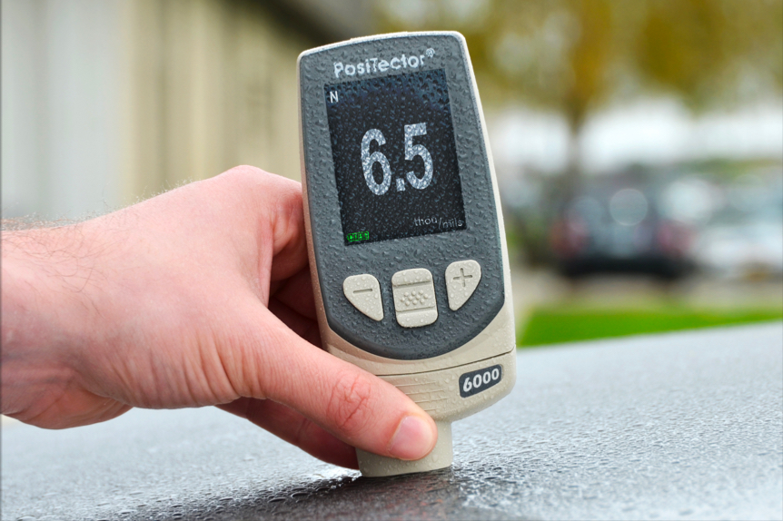 Close-up photo of a PosiTector 6000 mil gage measuring the paint thickness on a car hood