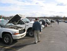 Photo of a man looking at a truck in a lot at a car auction