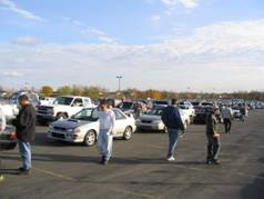 Photo of a people looking at cars in a lot at a car auction