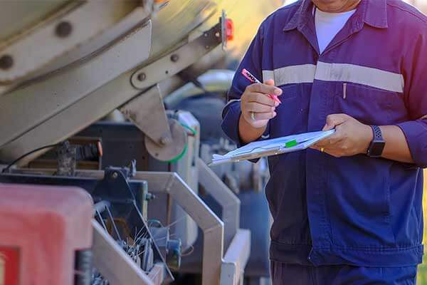 Photo—A registered inspector records his findings from the cargo tank he is inspecting