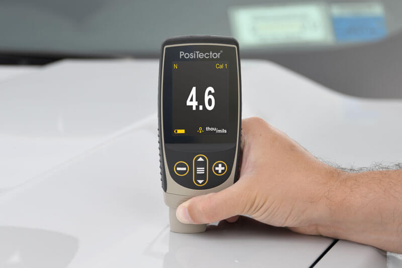 Photo of a PosiTector 6000 FN1 taking a paint thickness measurement on an automobile hood