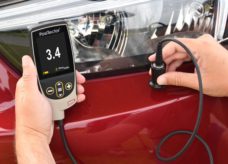 Photo of a PosiTector 200 B1 Ultrasonic Coating Thickness Gage measuring on a plastic bumper