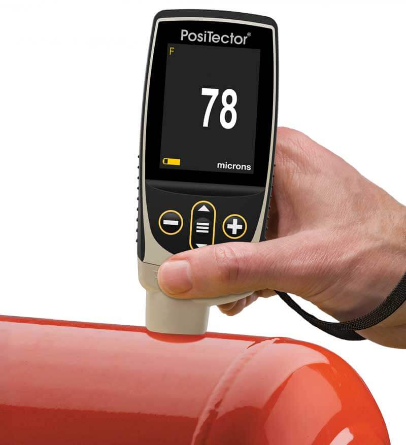 Photo of a PosiTector 6000 FN measuring paint thickness on a red tank