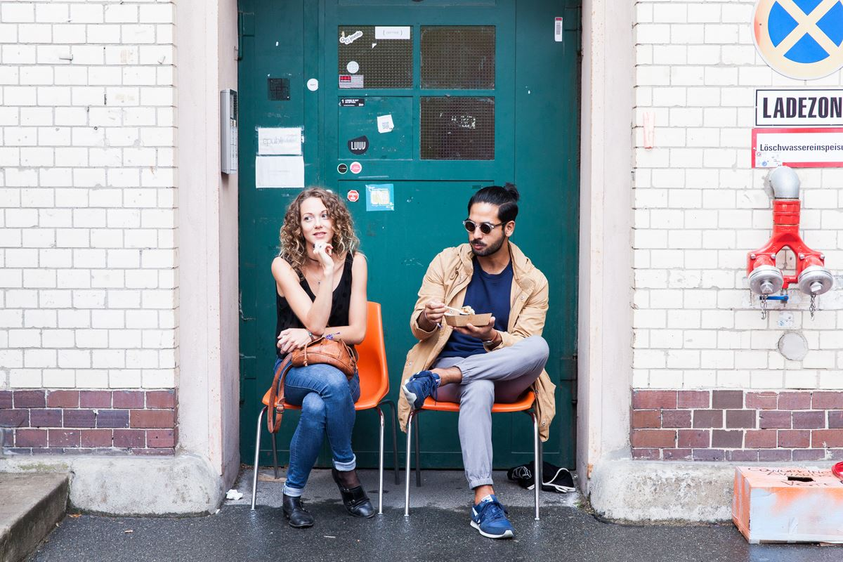 female business entrepreneur siting and talking with a male community manager in front of a green door of betahaus kreuzberg coworking space