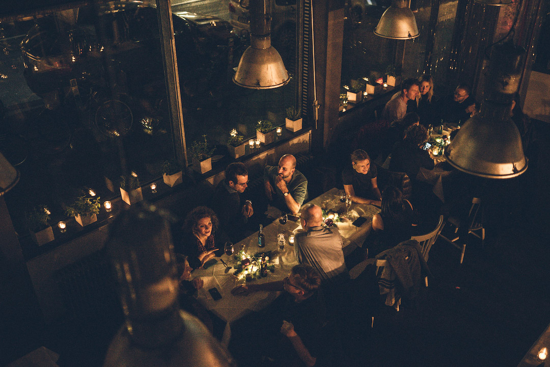 people participating in an event, dinning and talking inside the betahaus café at night