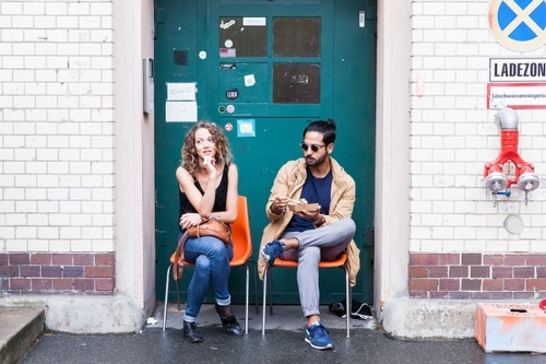 Two entrepeneurs sit by a green door of betahaus coworking space in Moritzplatz at an event