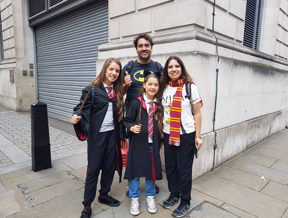 family standing out side Ministry of Magic  wearing Harry Potter Scarves On a Harry Potter Taxi Tour with Visit London Taxi Tours