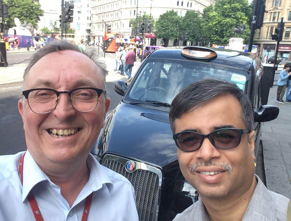 Taxi guide with happy guest standing by  taxi on London layover tour with visit london taxi tours
