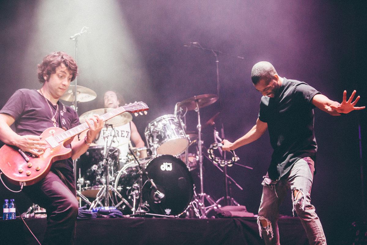 El artista Trombone Shorty toca la pandereta sobre el escario junto a su baterista y su guitarrista