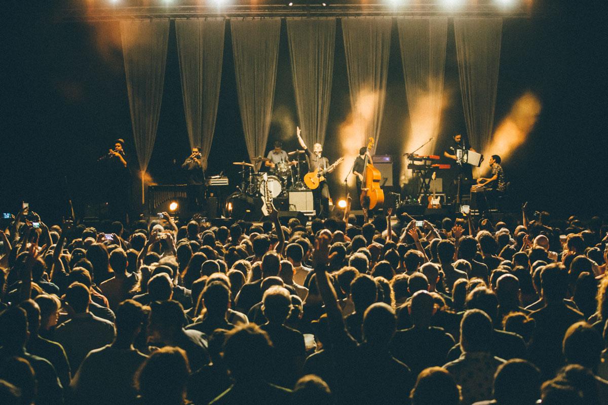 La banda Calexico actúa frente a un público lleno sobre el escenario