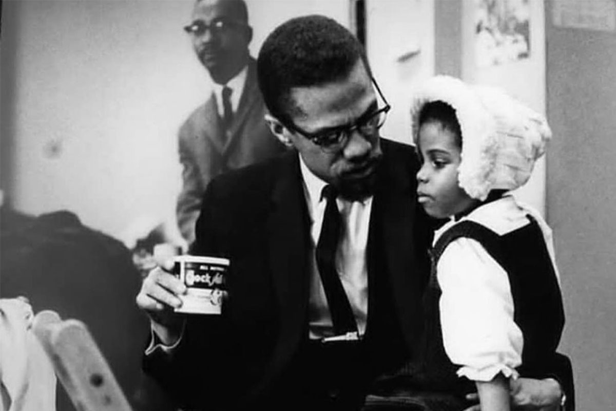 El activista Malcolm X con su hija pequeña sentada en su regazo