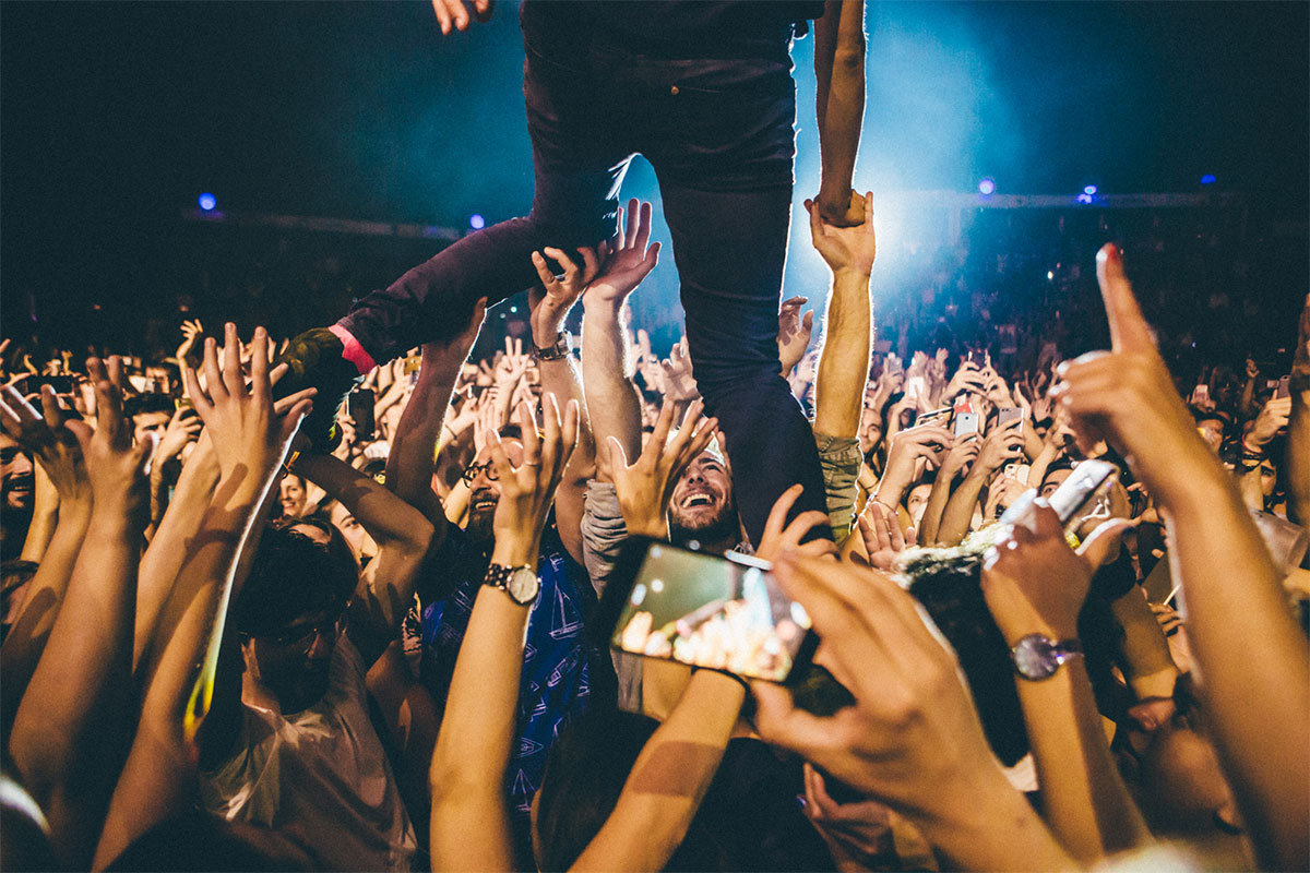 Artista siendo sujetado por un público masivo durante una actuación
