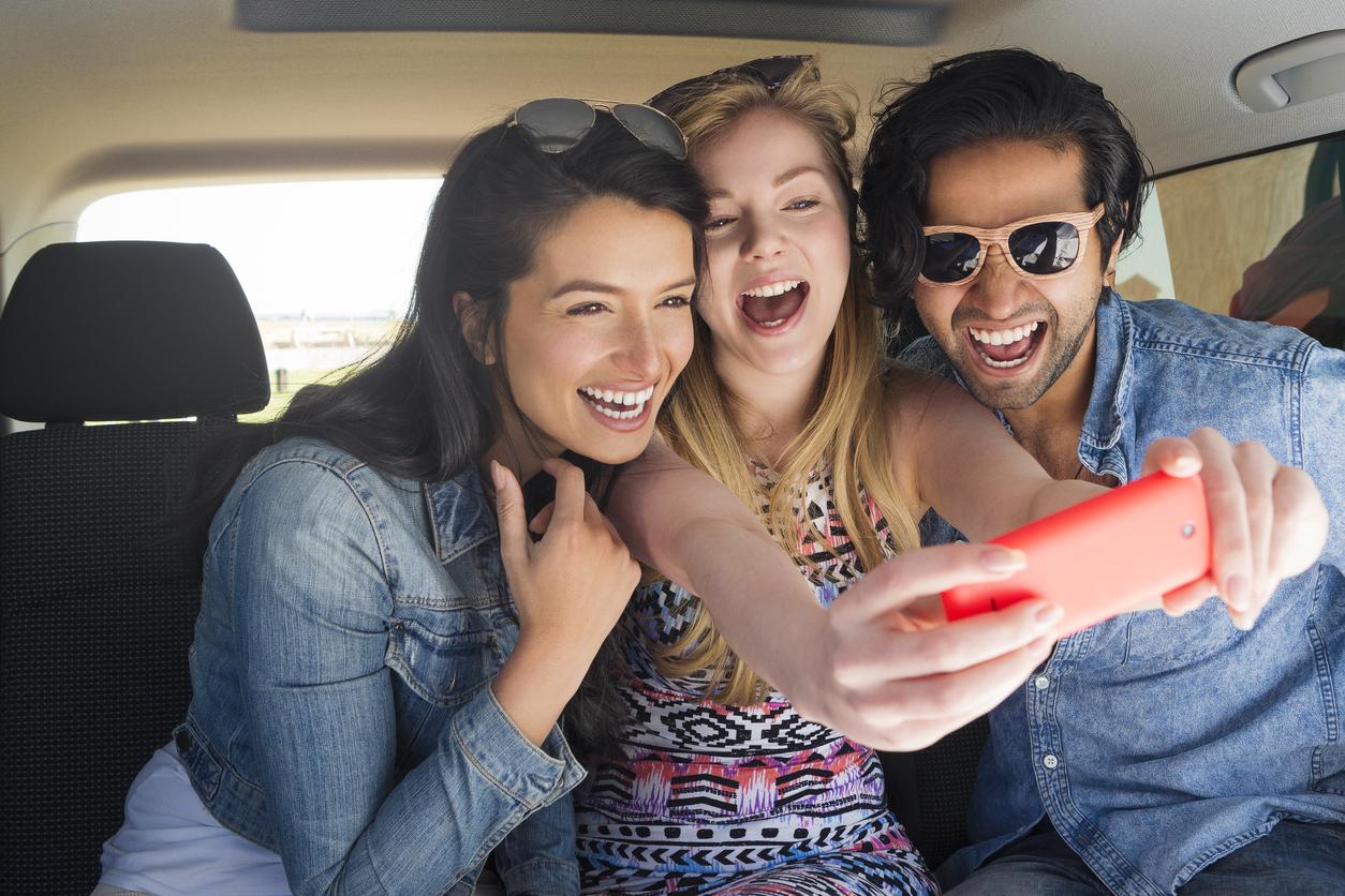 Dos chicas y un chico se divierten tomándose una foto selfie en un coche