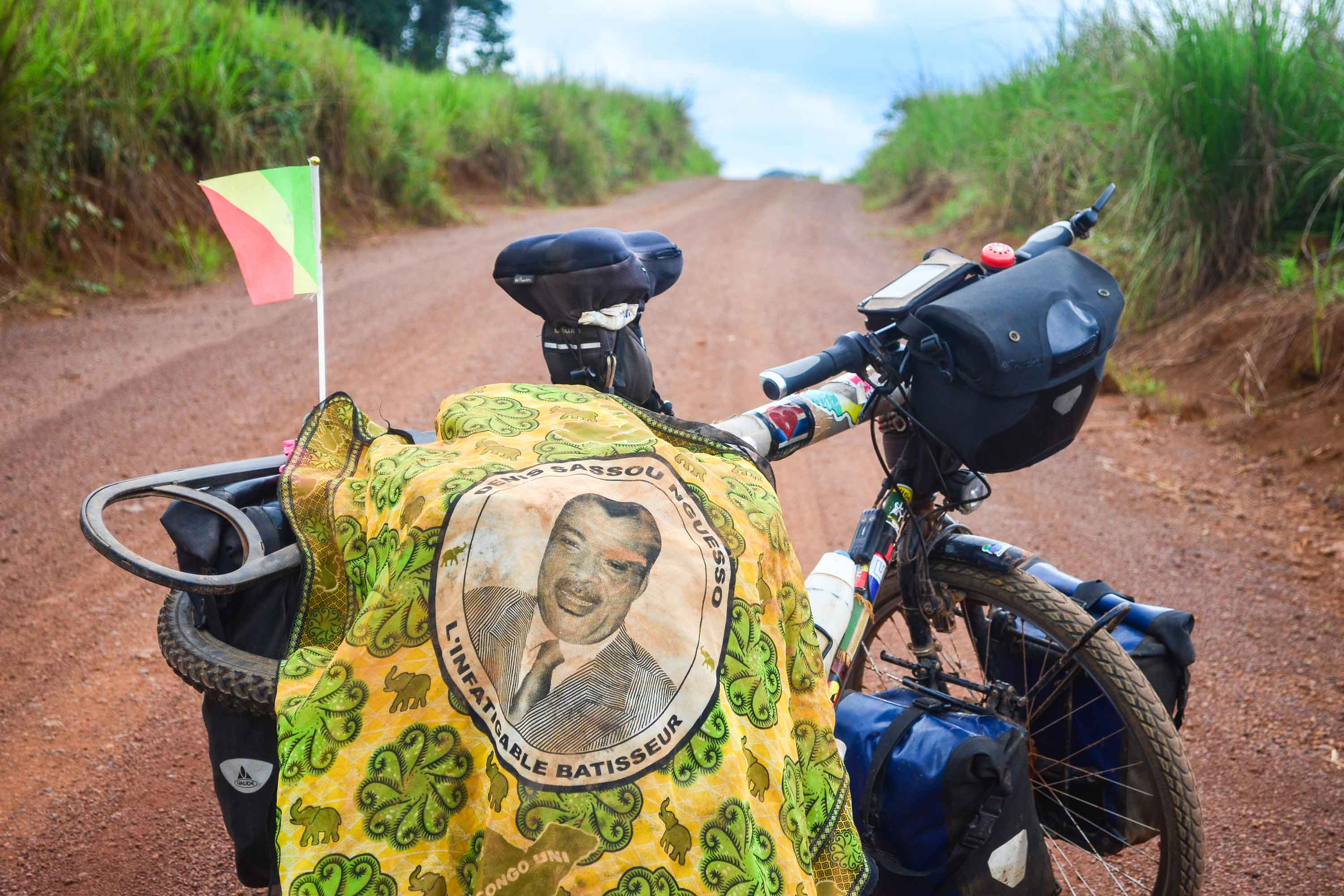 A flag with a portrait of Congo's President, Denis Sassou Nguesso, lies draped over a road bike.