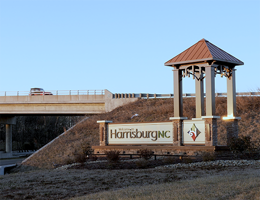 Cars pass the Harrisburg sign on the main thoroughfare into town