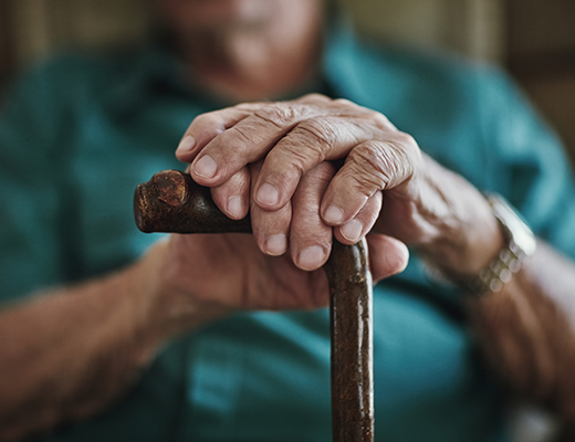 Elderly hands clutch a cane