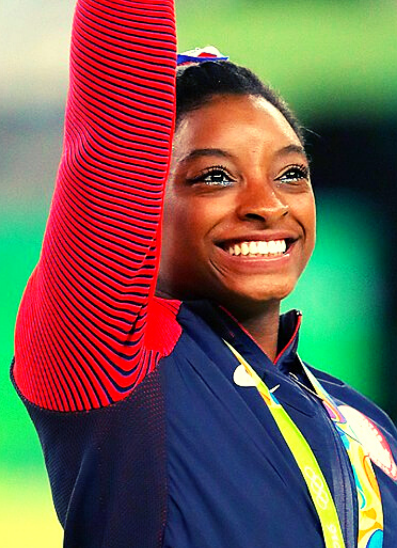Simone Biles smiling and lifting her arm triumphantly