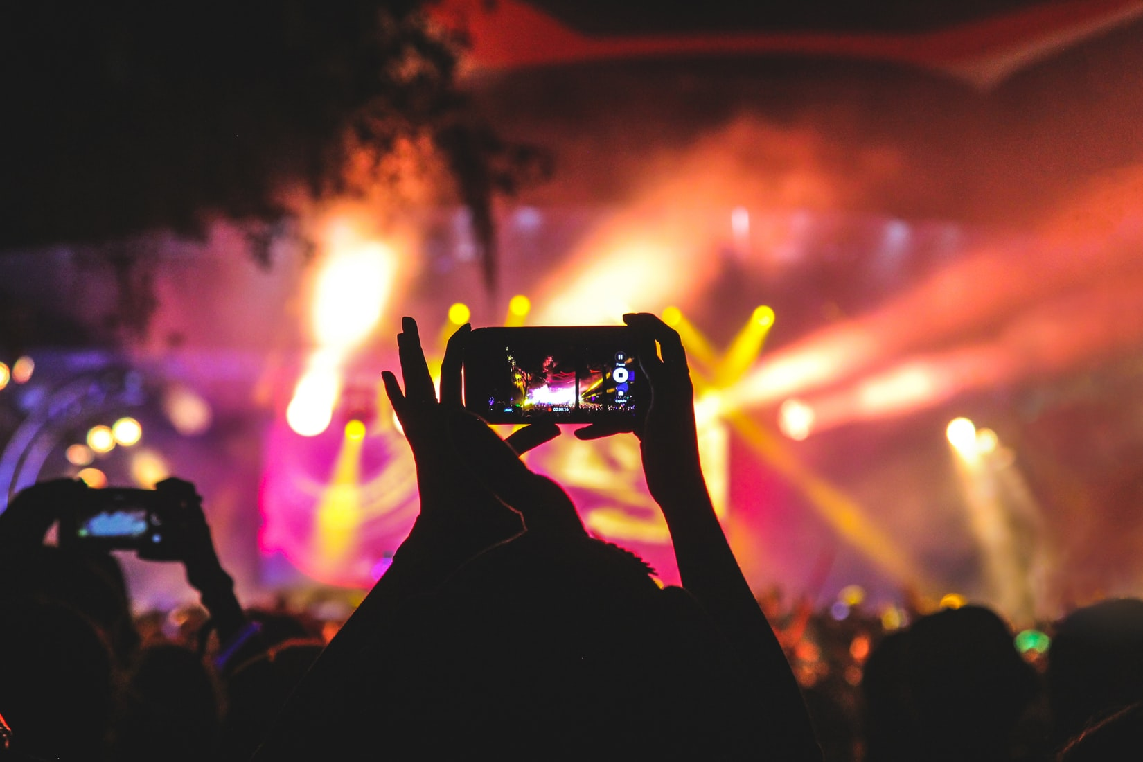 an image of a pair of hands holding a cell phone to take a picture at a concert