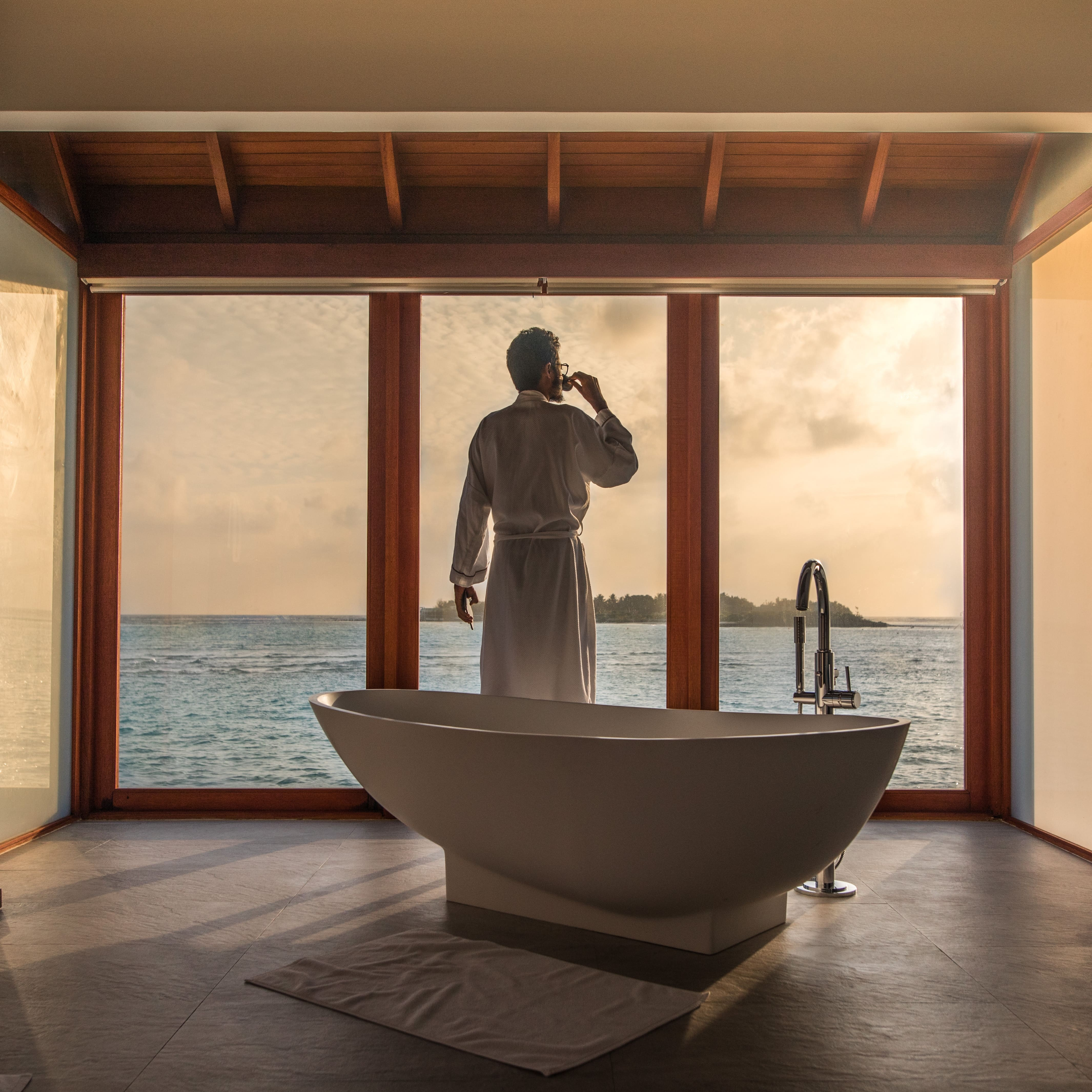 an image of a man in a robe drinking coffee next to a bathtub looking out over the ocean