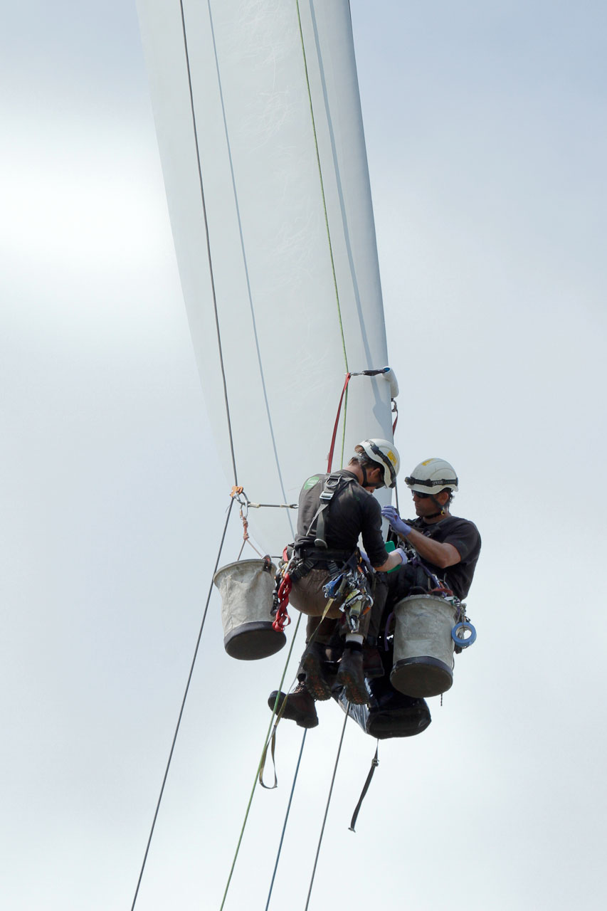 Two technicians repair wind turbine blade tip