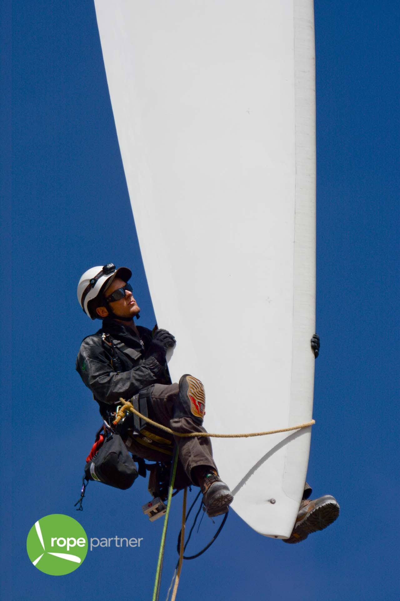 Technician inspects wind turbine blade trailing edge for damages