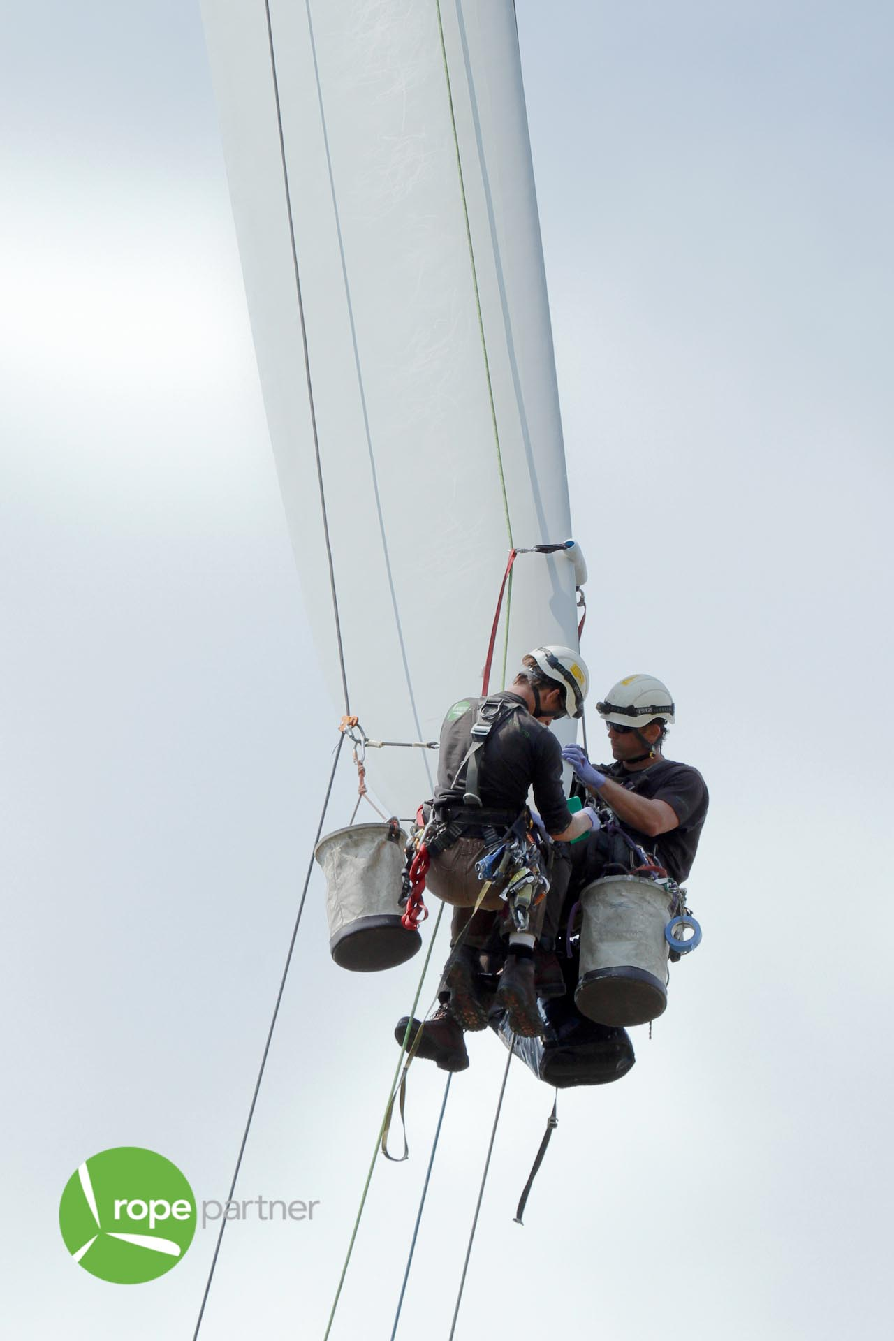 Two Technicians Repair Damaged Wind Turbine Blade